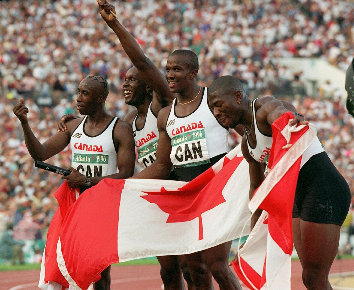 Relay waving to crowd and holding Canadian flag