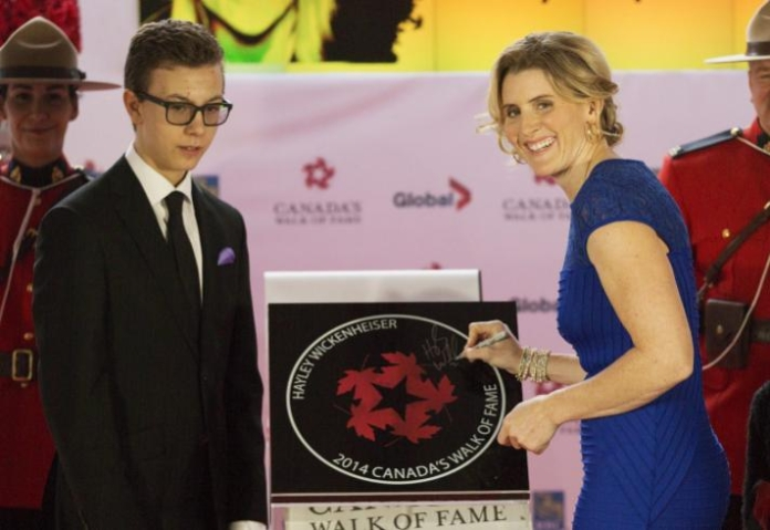 With the help of her son Noah Pacina, hockey Olympian Hayley Wickenheiser, right, is inducted into Canada's Walk of Fame in Toronto on Saturday, October 18, 2014. THE CANADIAN PRESS/Michelle Siu