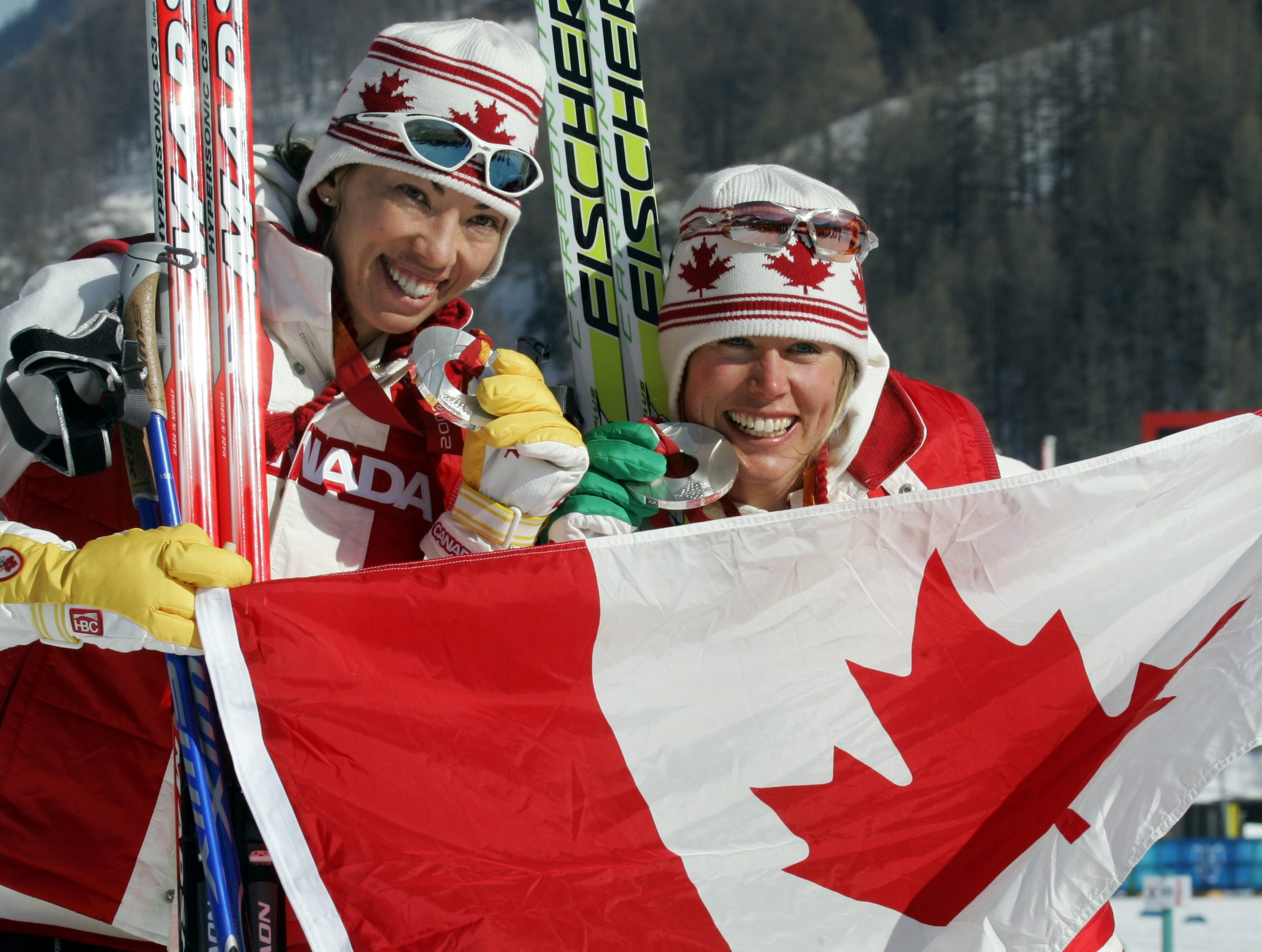 Beckie Scott, left, and Sara Renner pose with the Canadian flag as they display their silver medals