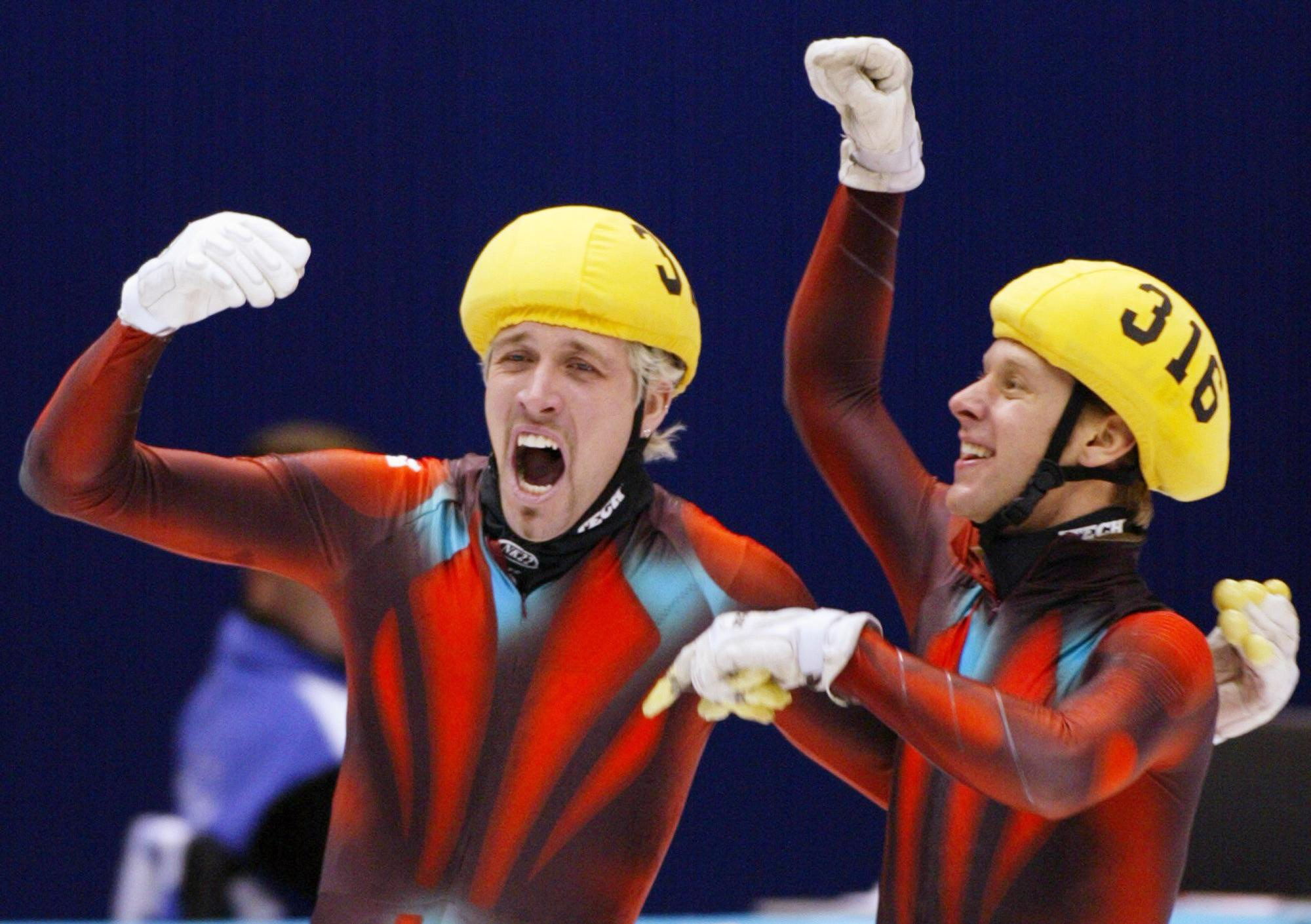Two speed skaters celebrate with arms up