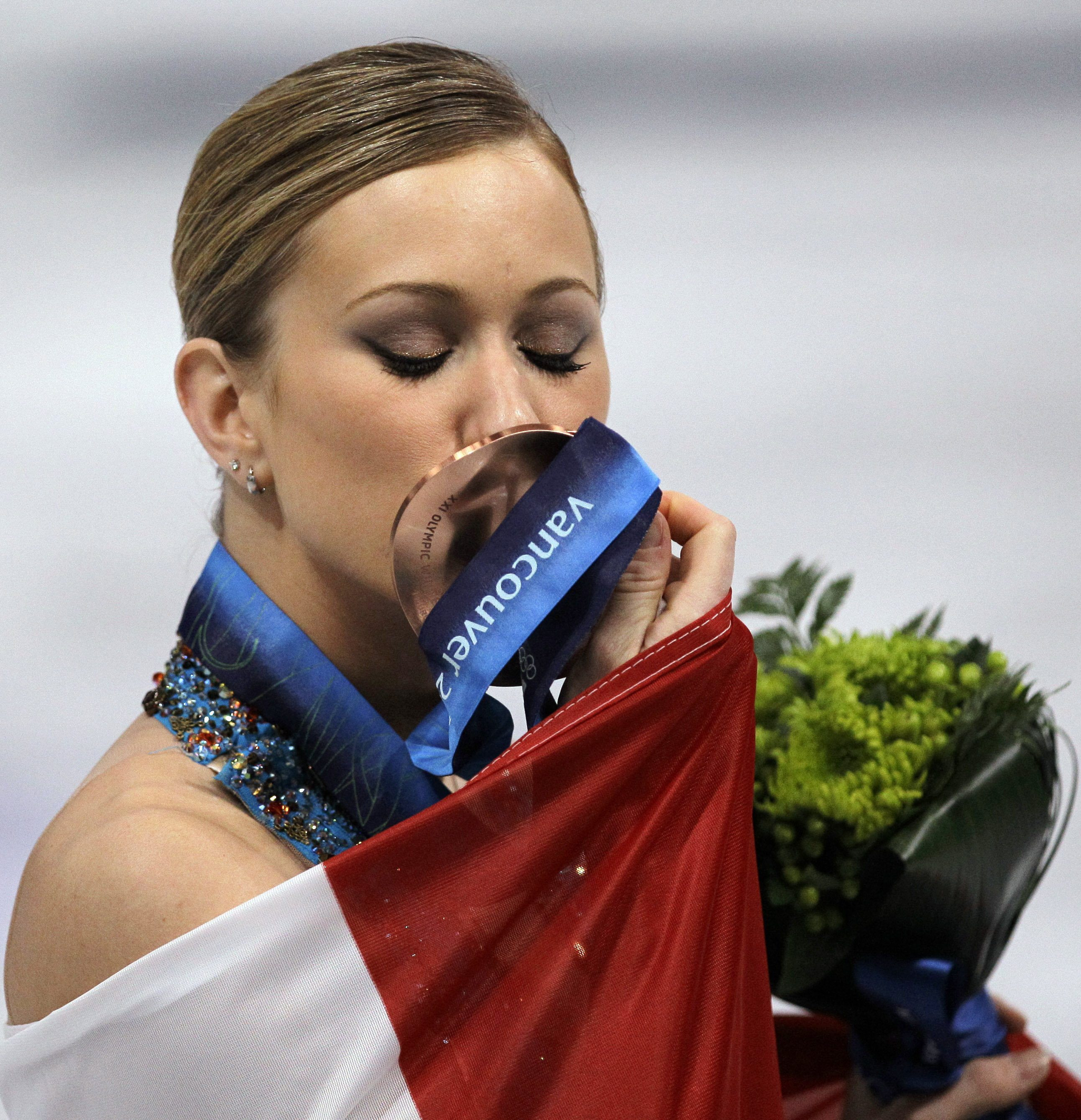 Joannie Rochette kisses her bronze medal during the victory celebration at the Vancouver 2010 Olympics