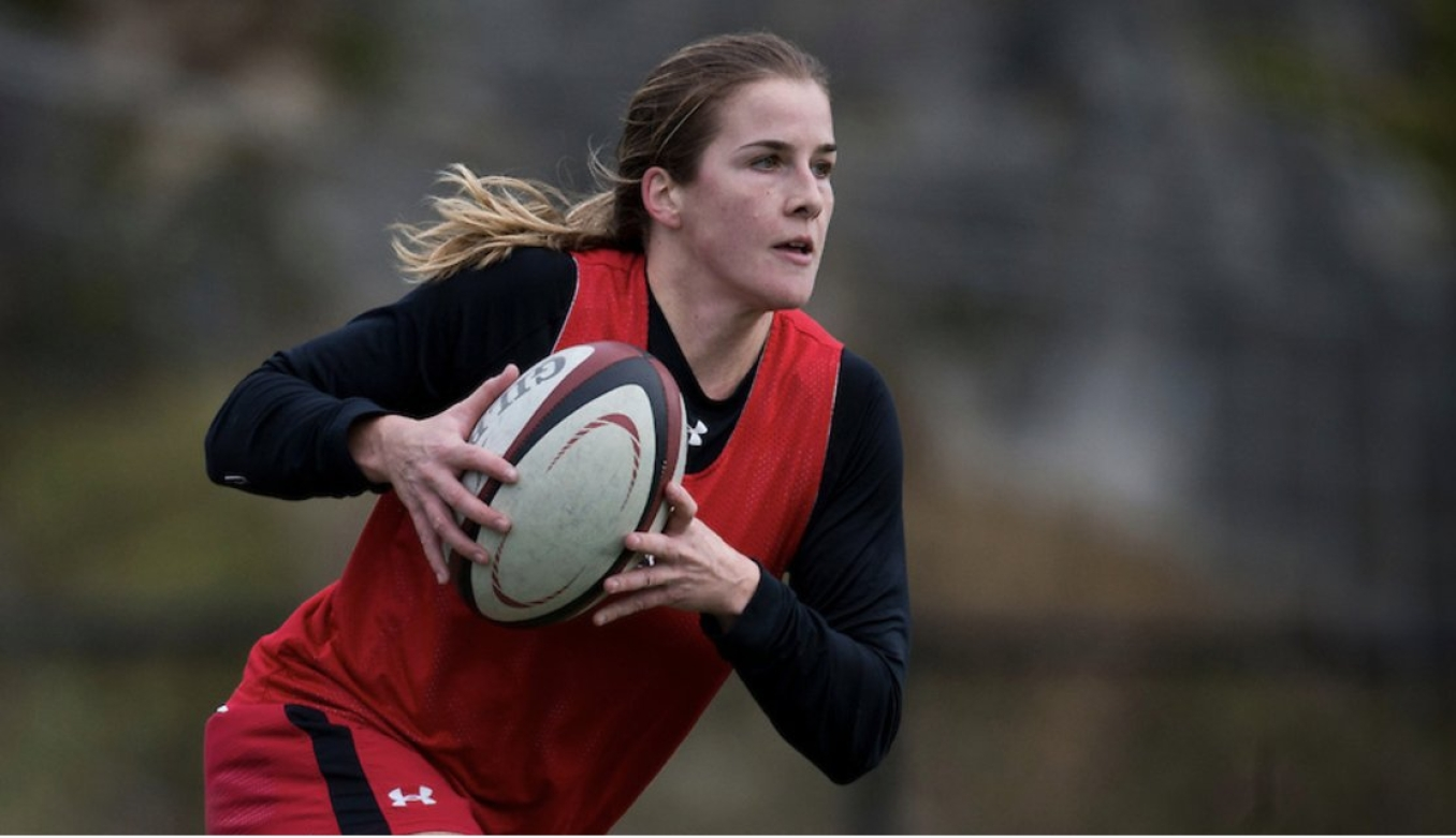 Nadia Popov runs with the ball during a rugby match.