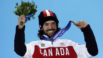 Charles Hamelin on the podium at Sochi, holding up flowers in his right hand and his medal in the other.