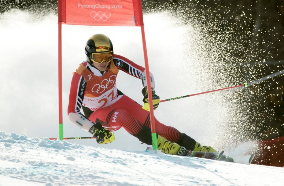 Erik Read mid-competition in the giant slalom at PyeongChang 2018. He is wearing a red, orange and white suit, and a chrome yellow helmet with matching goggles.