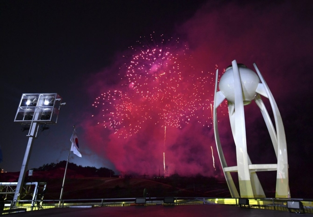 Fireworks explode near the Olympic cauldron after the flame was extinguished at the conclusion of the closing ceremony of the 2018 Winter Olympics in Pyeongchang, South Korea, Sunday, Feb. 25, 2018. (Florien Choblet/Pool Photo via AP)