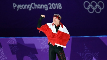 Ted-Jan Bloeman waves to the crowd with a Canadian flag wrapped around him after winning gold in the men's 10000m final at the 2018 winter Olympics.