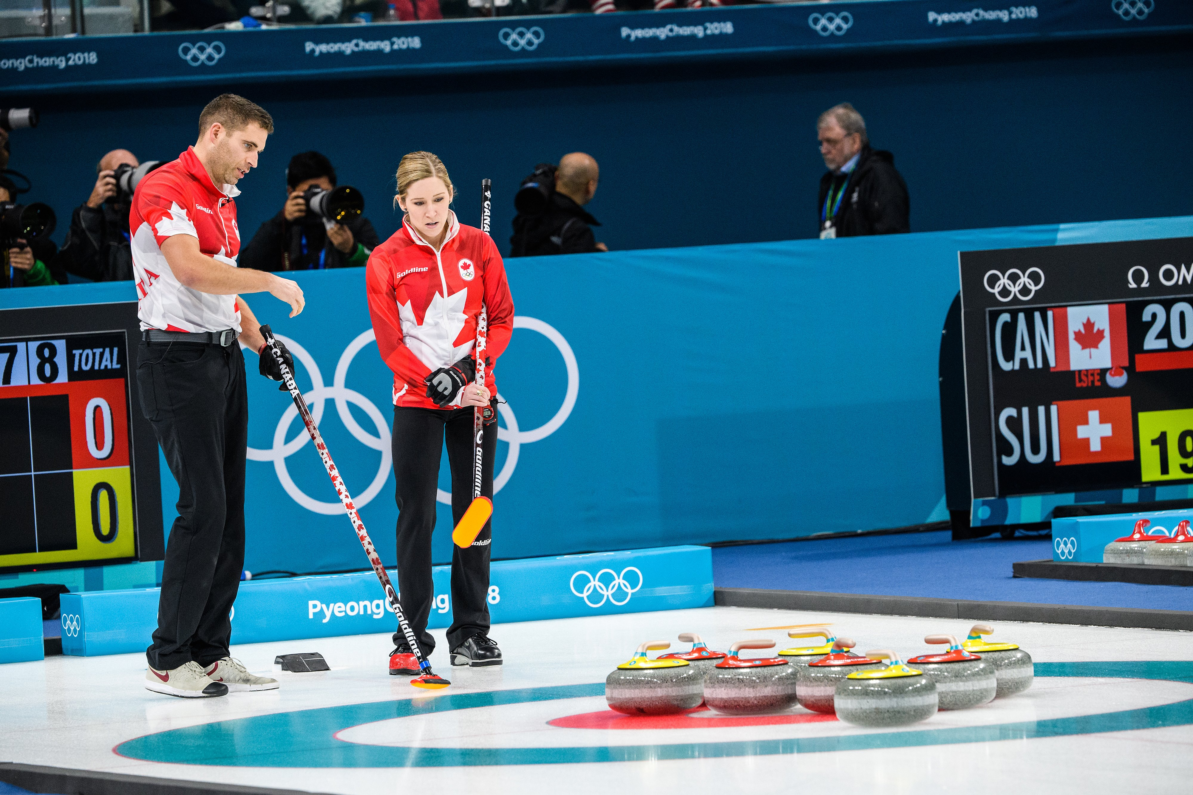 Two curlers look at the rocks in the rings