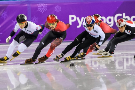 Four short track speed skaters racing