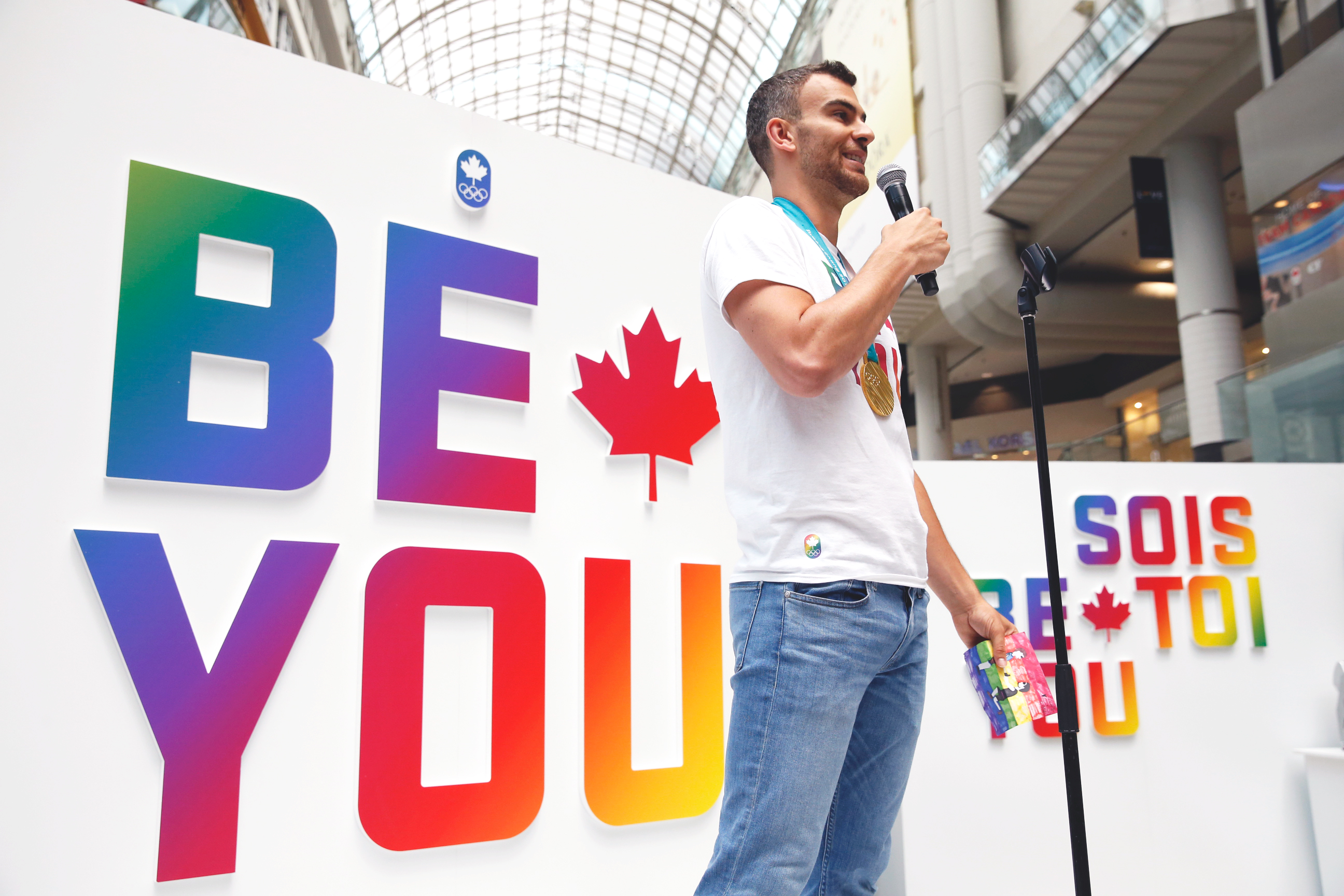 Eric Radford stands in front of Be You sign and speaks to the crowd.