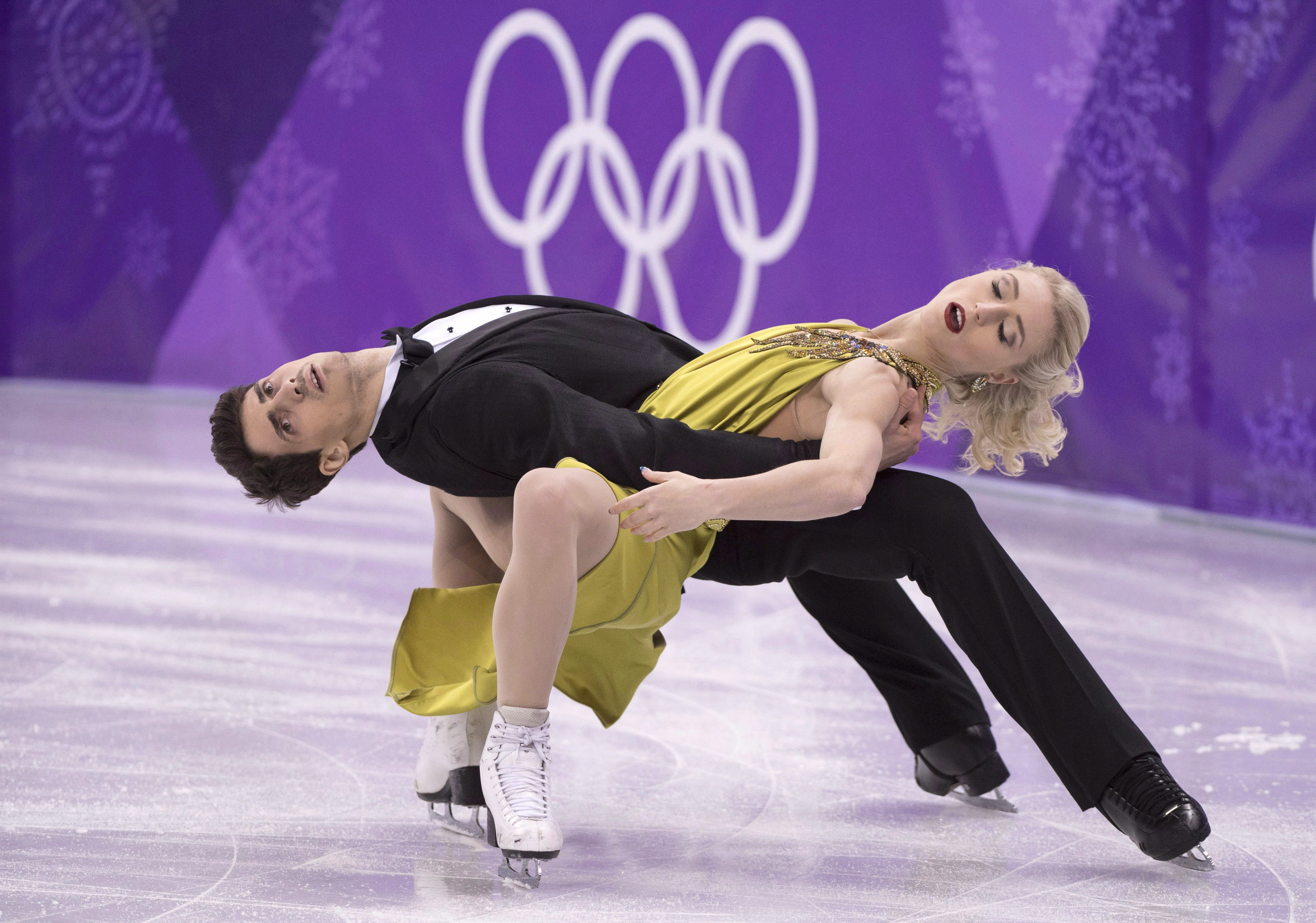 Two figure skaters in a low to the ice move