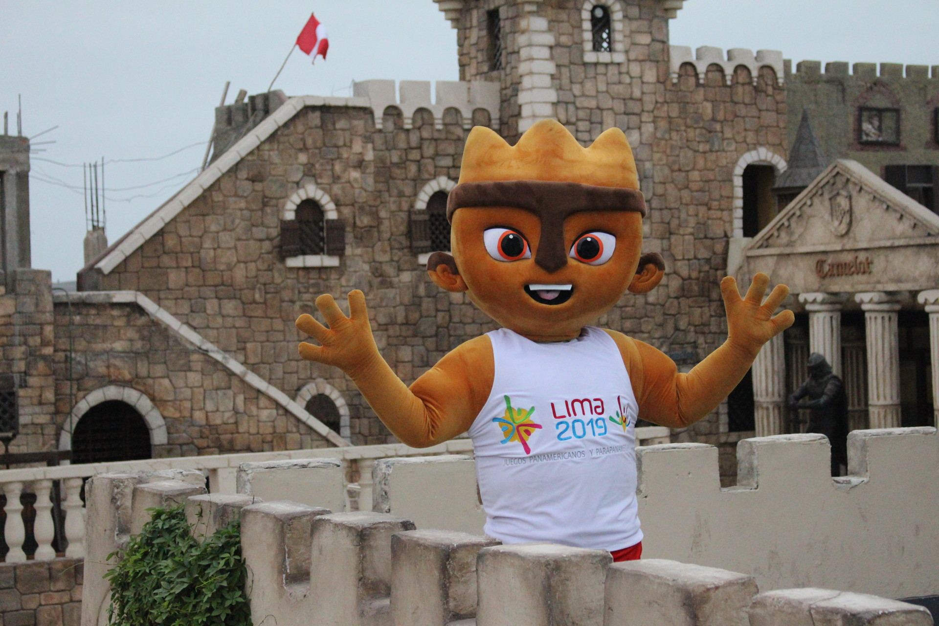 The Lima mascot standing in front of a castle like building