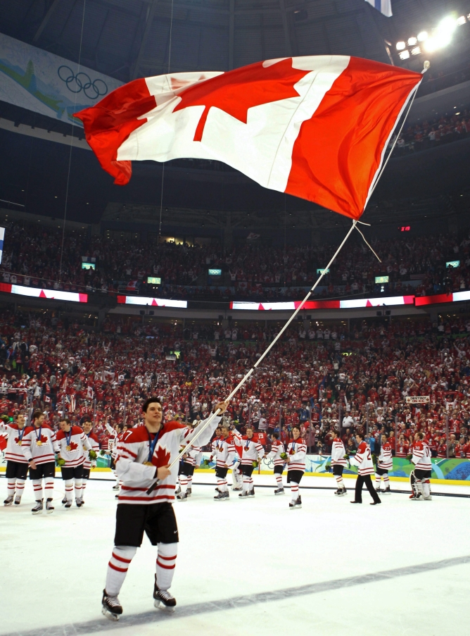 Canada's Sidney Crosby skates with tha flag after scoring the overtime winning goal in men's ice hockey gold medal final at the 2010 Winter Olympic Games in Vancouver, Sunday, Feb. 28, 2010. THE CANADIAN PRESS/Jonathan Hayward