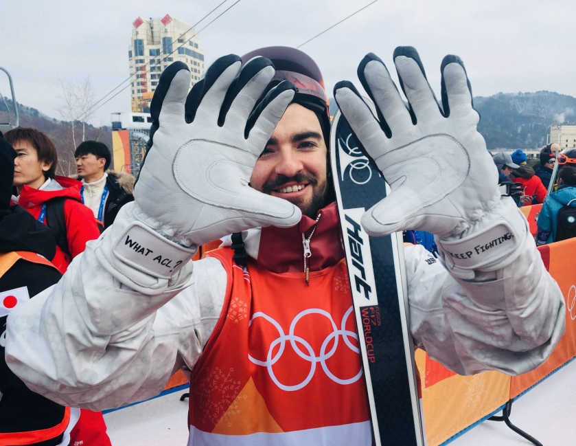Philippe Marquis, of Canada, shows his motivational notes he wrote on his gloves before qualifying for the men's moguls at Phoenix Snow Park at the 2018 Winter Olympics in Pyeongchang, South Korea, Friday, Feb. 9, 2018. Marquis earned a spot in the finals by finishing eighth in the 30-man field a month removed from tearing the ACL in his right knee. (AP Photo/Will Graves)