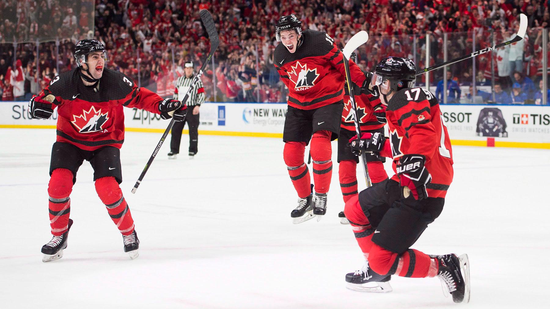 Trois joueurs célèbrent un but lors d'un match de hockey sur glace.