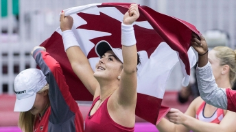 Bianca Andreescu celebrates with a Canadian flag over her head