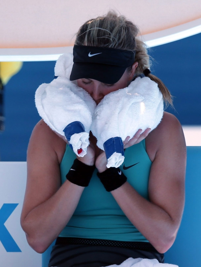 Eugenie Bouchard using ice in a towel to cool off at the 2014 Australian Open. (AP Photo/Aijaz Rahi)