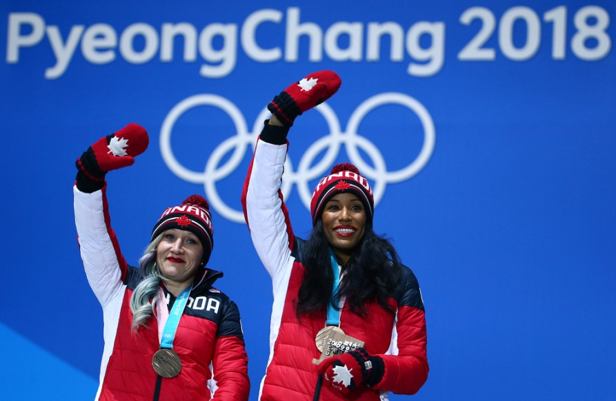 Kaillie Humpries and Phylicia George wave to the crowd with their bronze