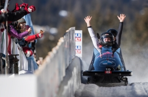Bobsledders raise their arms at the end of a run