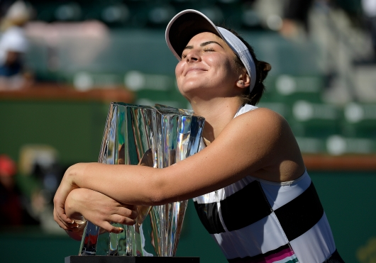 Bianca Andreescu, of Canada, smiles as she hugs her trophy
