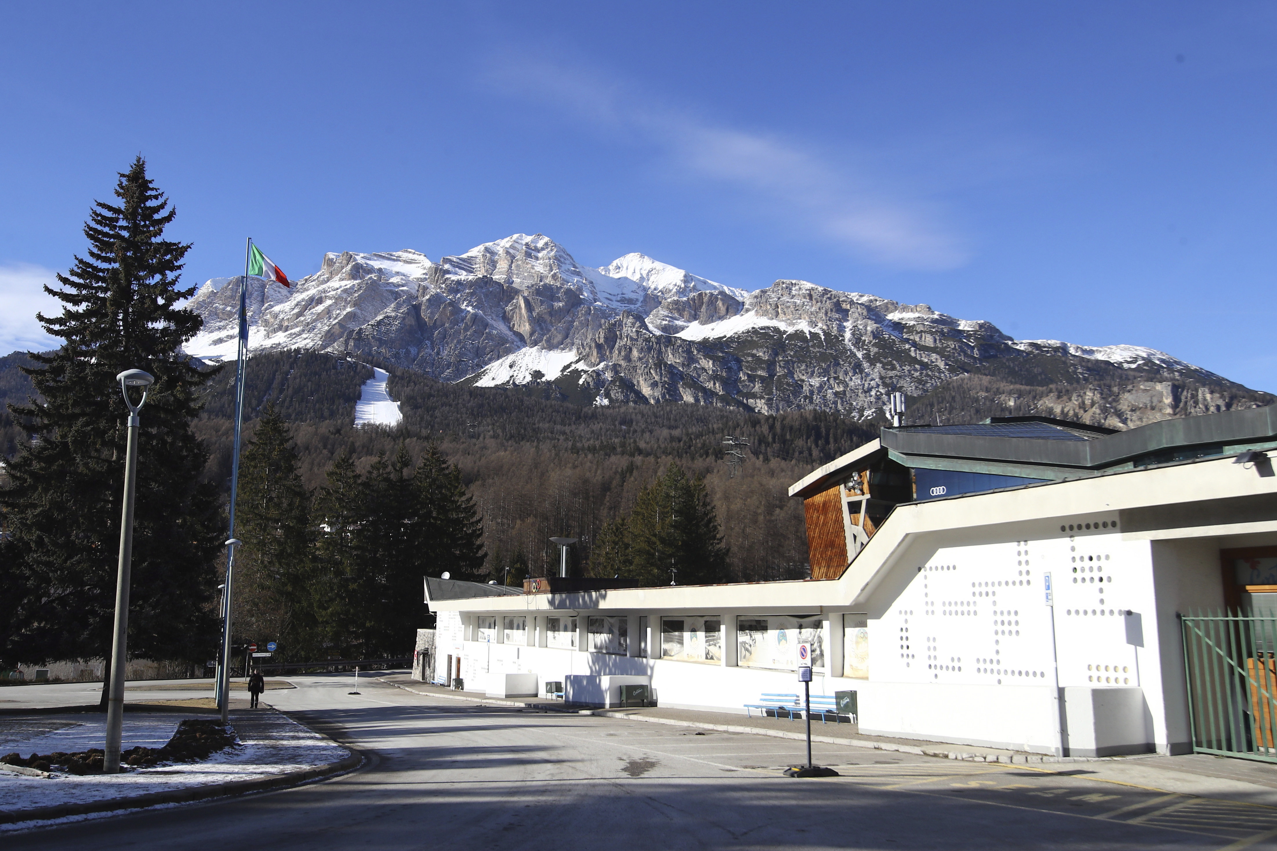 picture of building with snow covered mountain behind