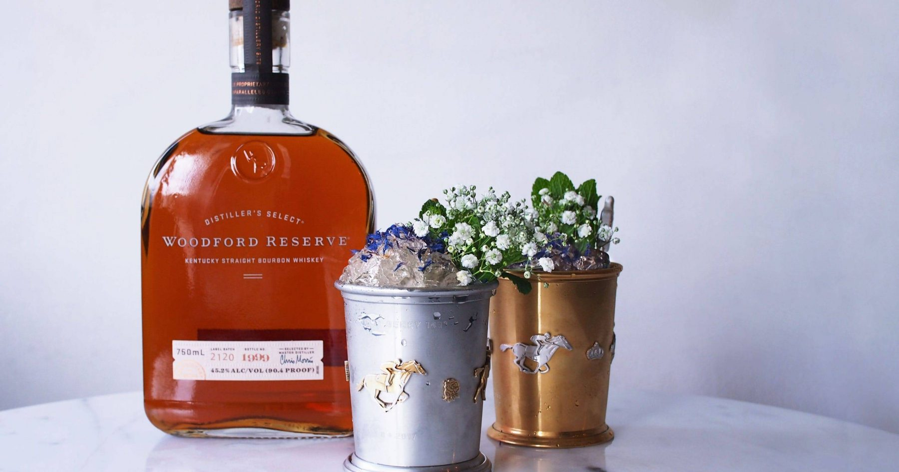 Mint Julep cup in a gold and silver cup with a bottle of Woodford Reserve behind