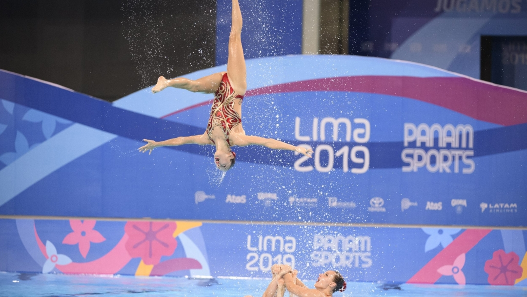 Artistic swimmer performs a flip in the air