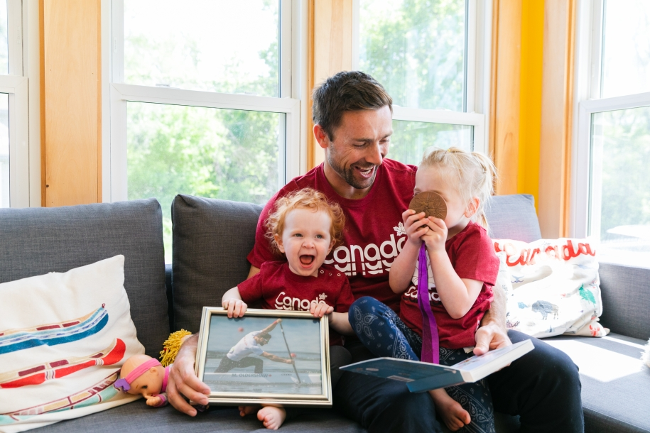 Father and children laughing on couch