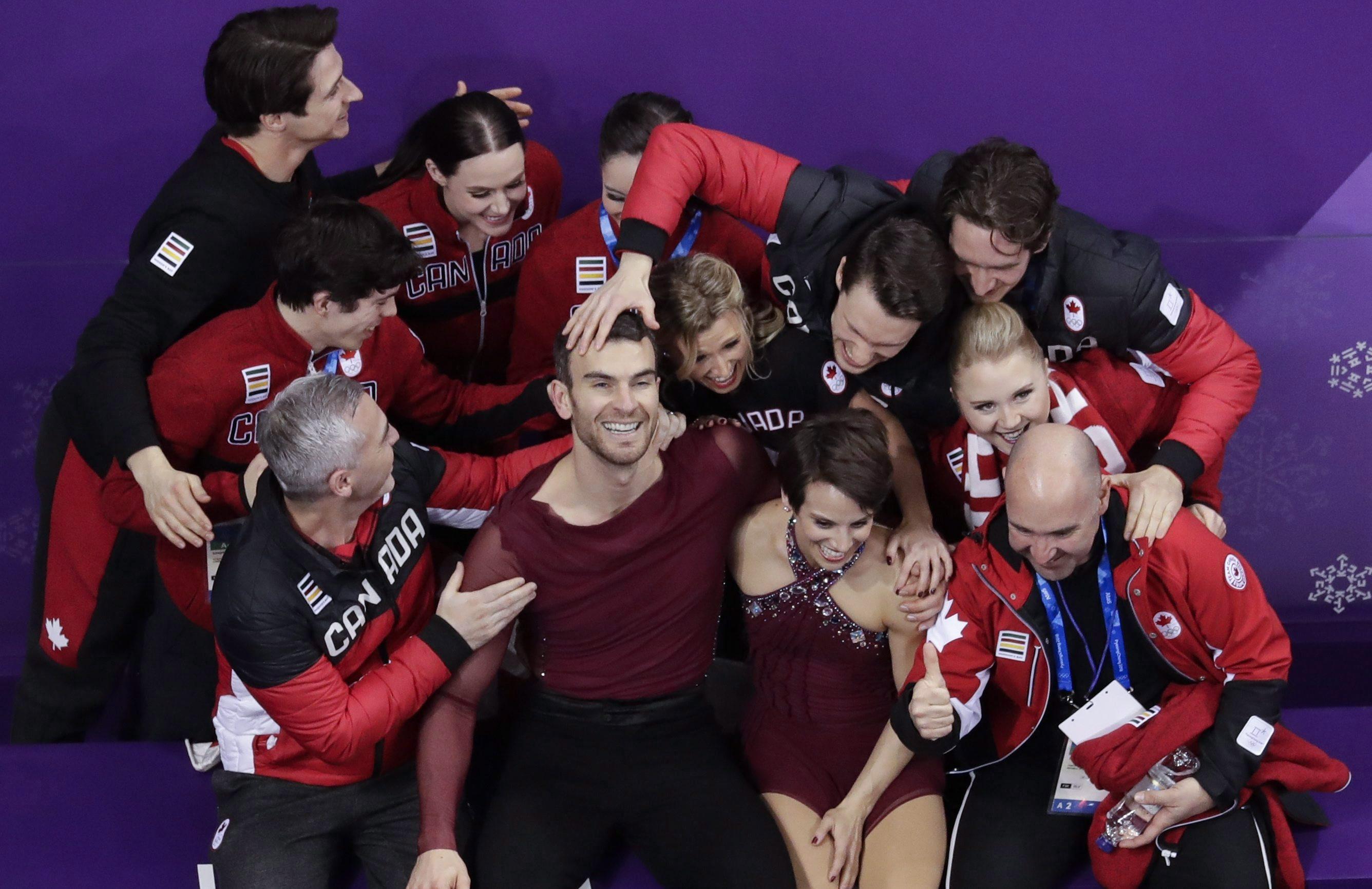 Meagan Duhamel and Eric Radford and Team Canada athletes celebrating after performance.