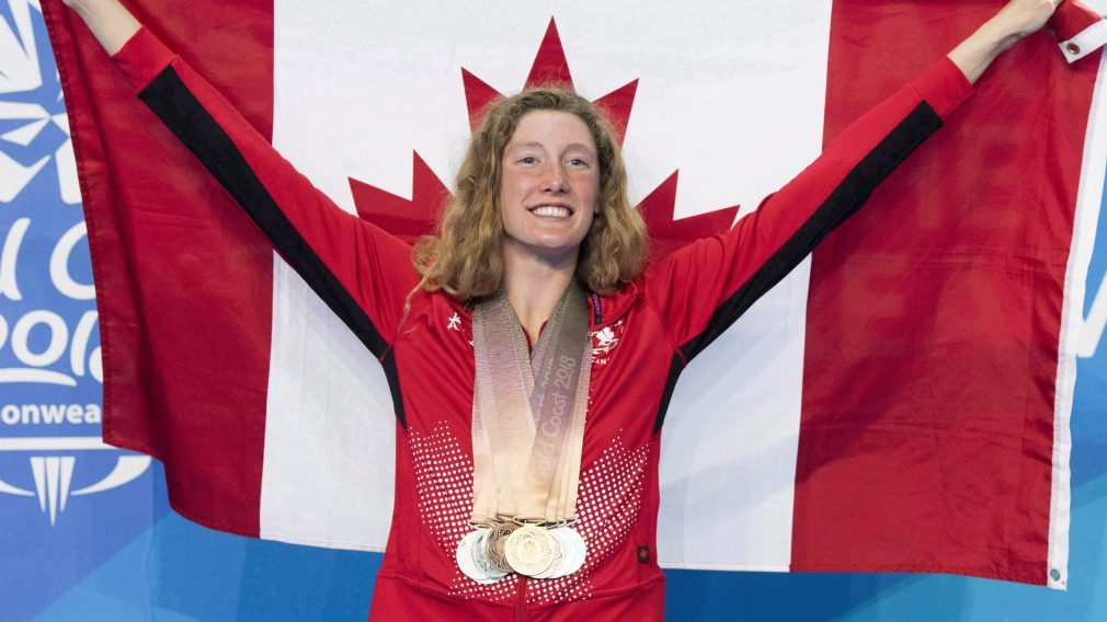Taylor Ruck poses for photos with her eight swimming medals