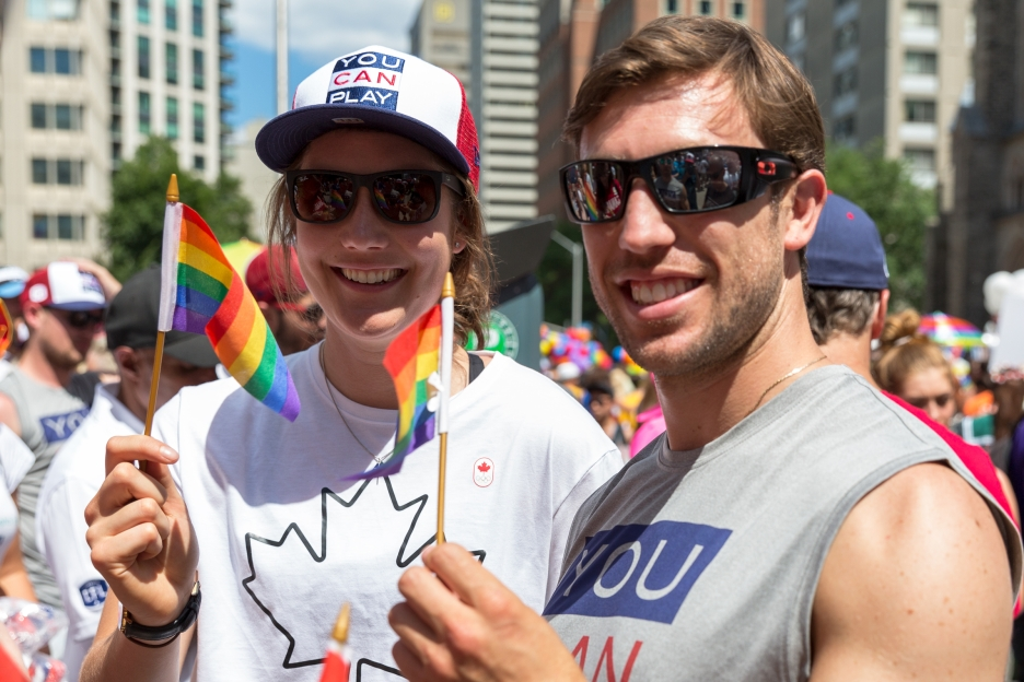 Anastasia Bucsis and Dylan Moscovitch wave small Pride flags at the 2017 Toronto Pride parade.