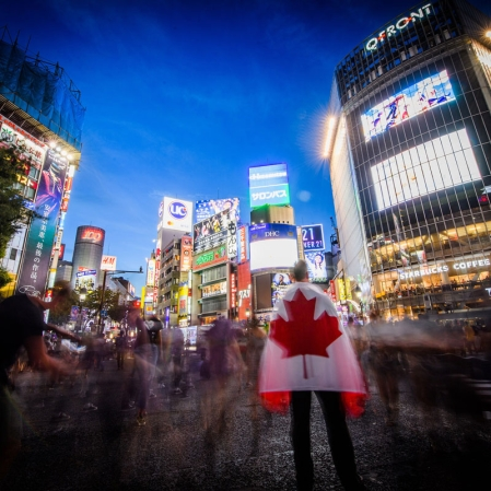 A man holding a Team Canada flag stares out at the crowds walking through Shibuya Crossing.