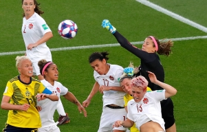 Canada's Stephanie Labbe leaps to punch the ball away.