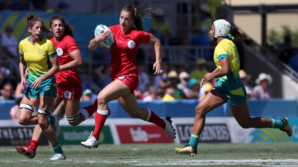 Canada's Caroline Crossley attempts to run past Australian defenders during their rugby sevens semifinal