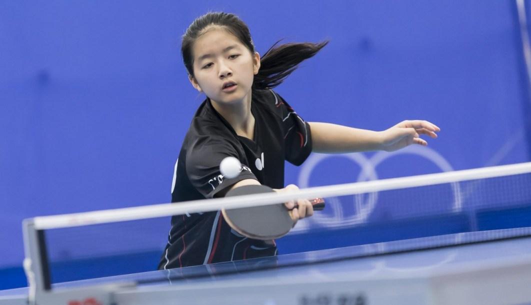 Table tennis player hits ball