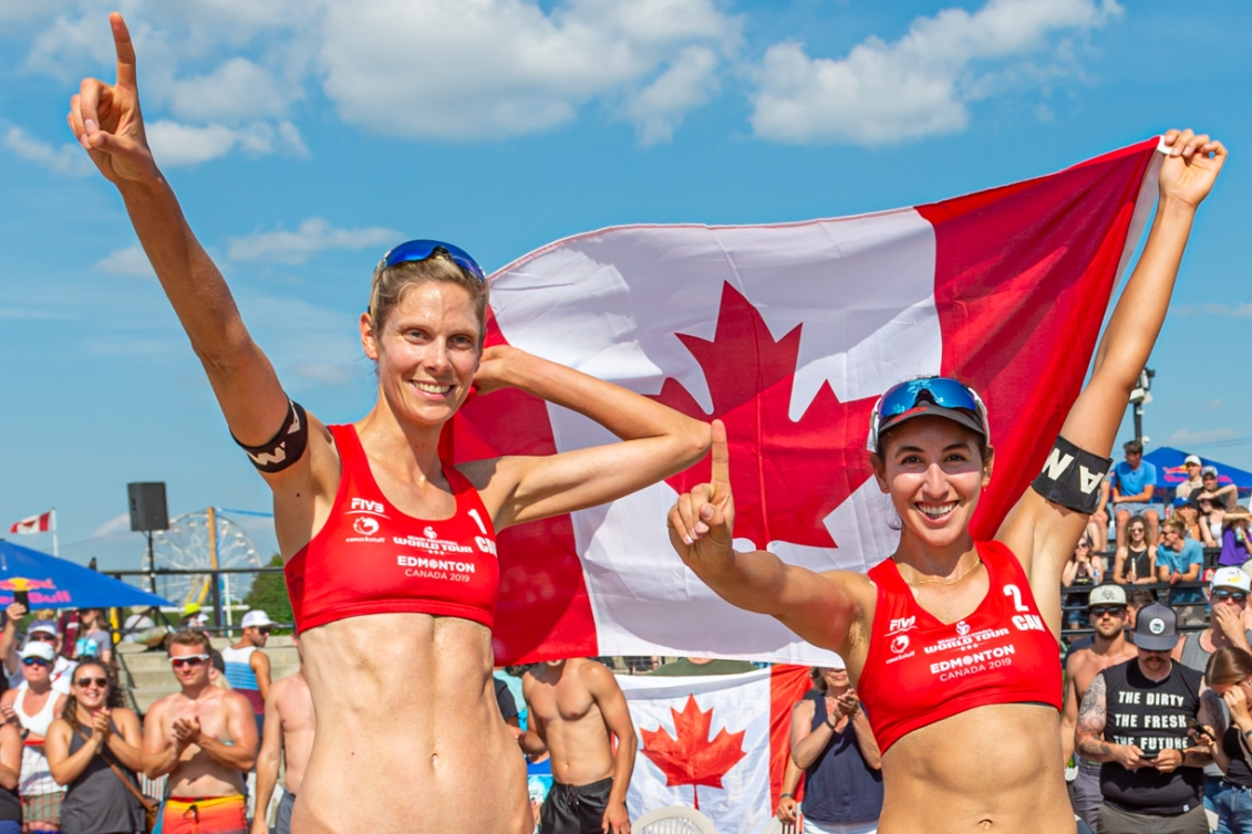 Sarah Pavan and Melissa Humana-Paredes hold the Canadian flag behind them and hold up their index finger to signal they are number one.