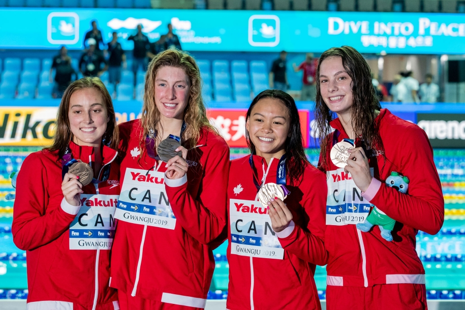 Four swimmers posing with medals