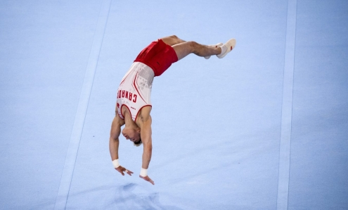 Male gymnast does a back handspring on the floor.