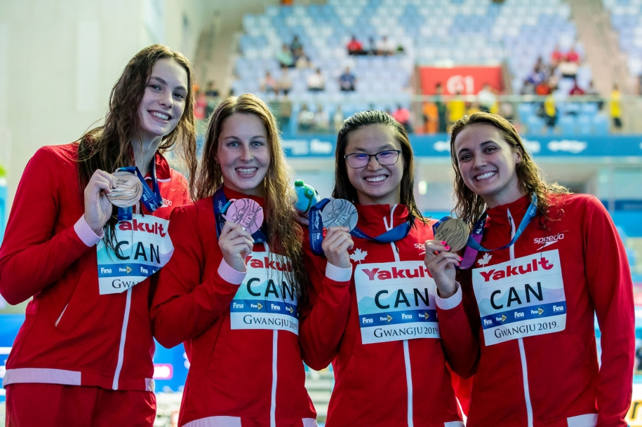 Four swimmers pose with medals