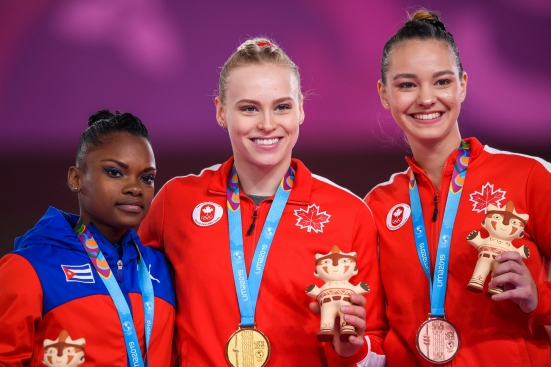 Three women pose with their gold, silver and bronze medals