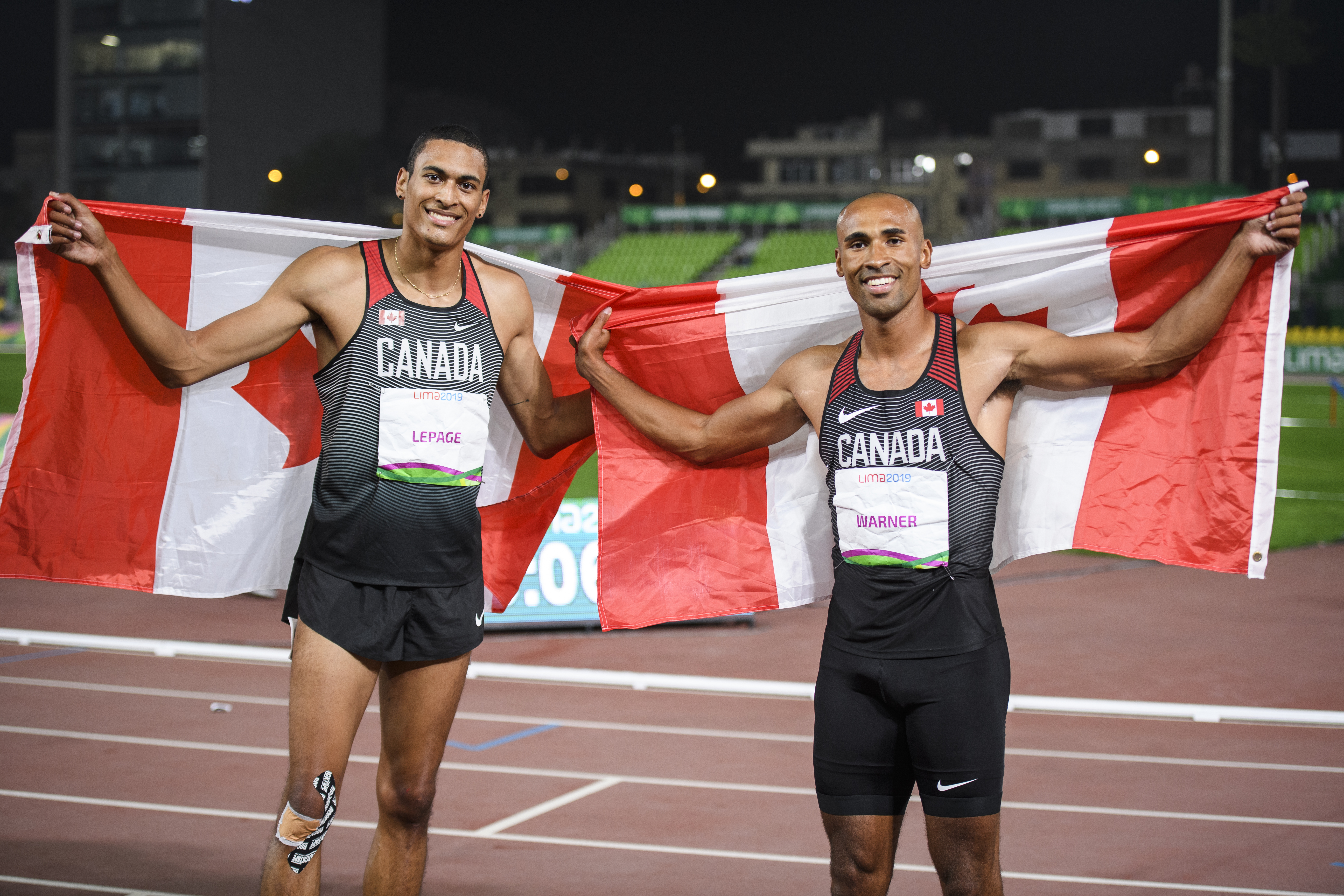 Pierce Lepage and Damian Warner take photo with Canadian flag