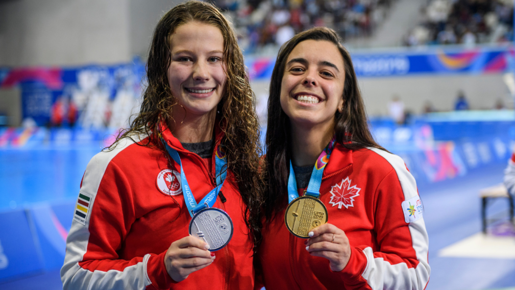Two athletes pose with medals