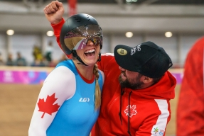 Kelsey Mitchell celebrates with her coach after winning the gold