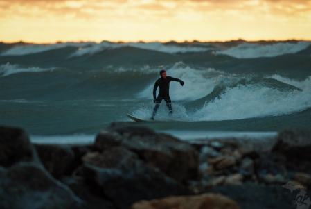 Surfer at sunset riding a wave