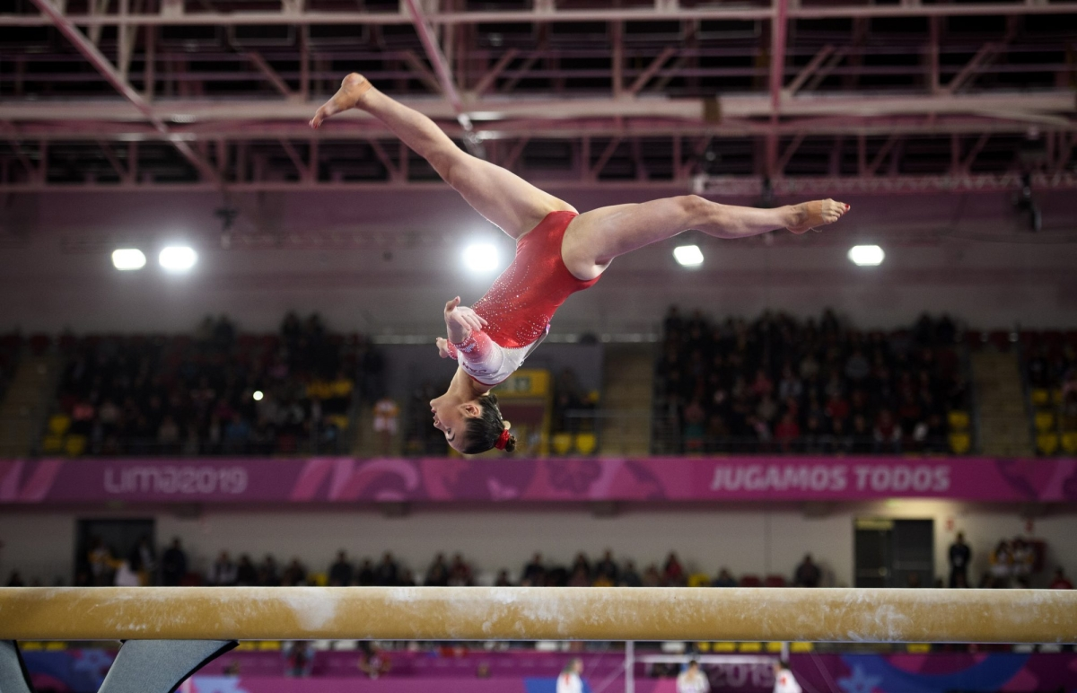 gymnast does a backflip on beam