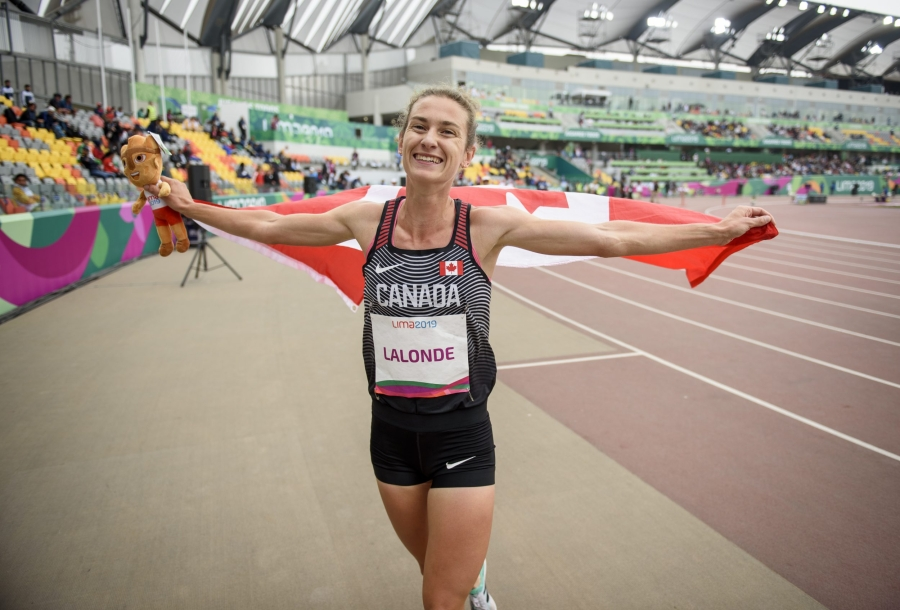 athlete smiles holding the Canadian flag
