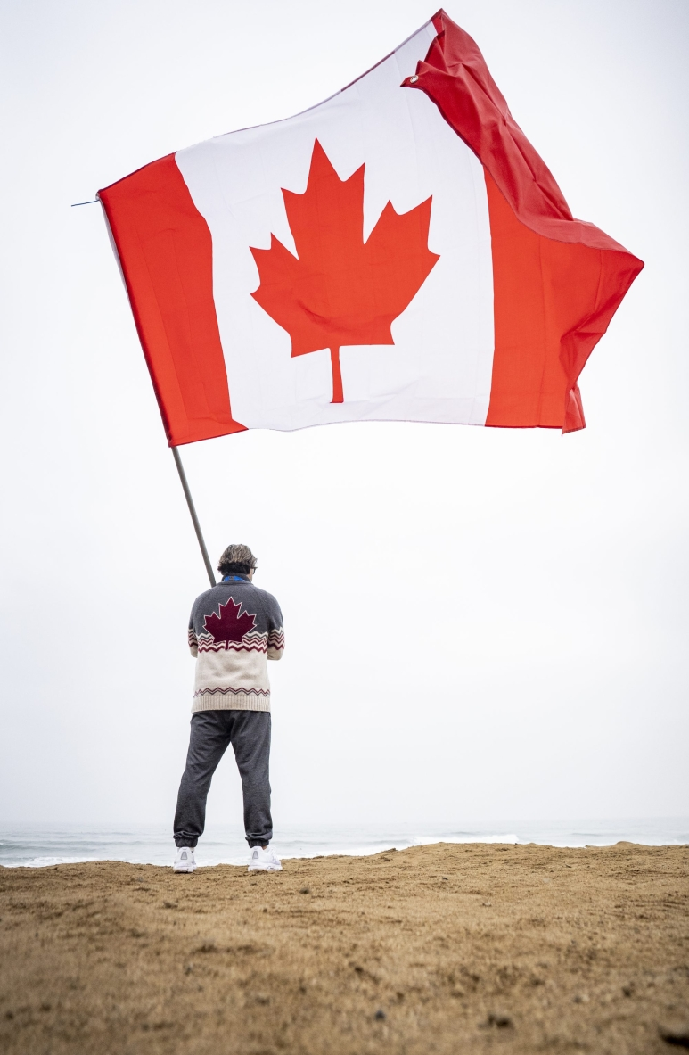 person holds a large canadian flag