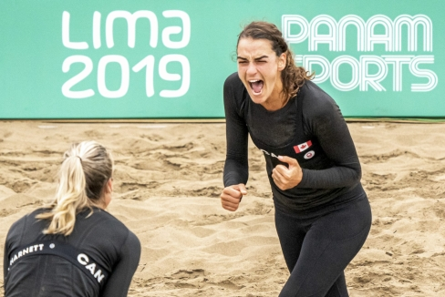 athlete celebrates a point in beach volleyball