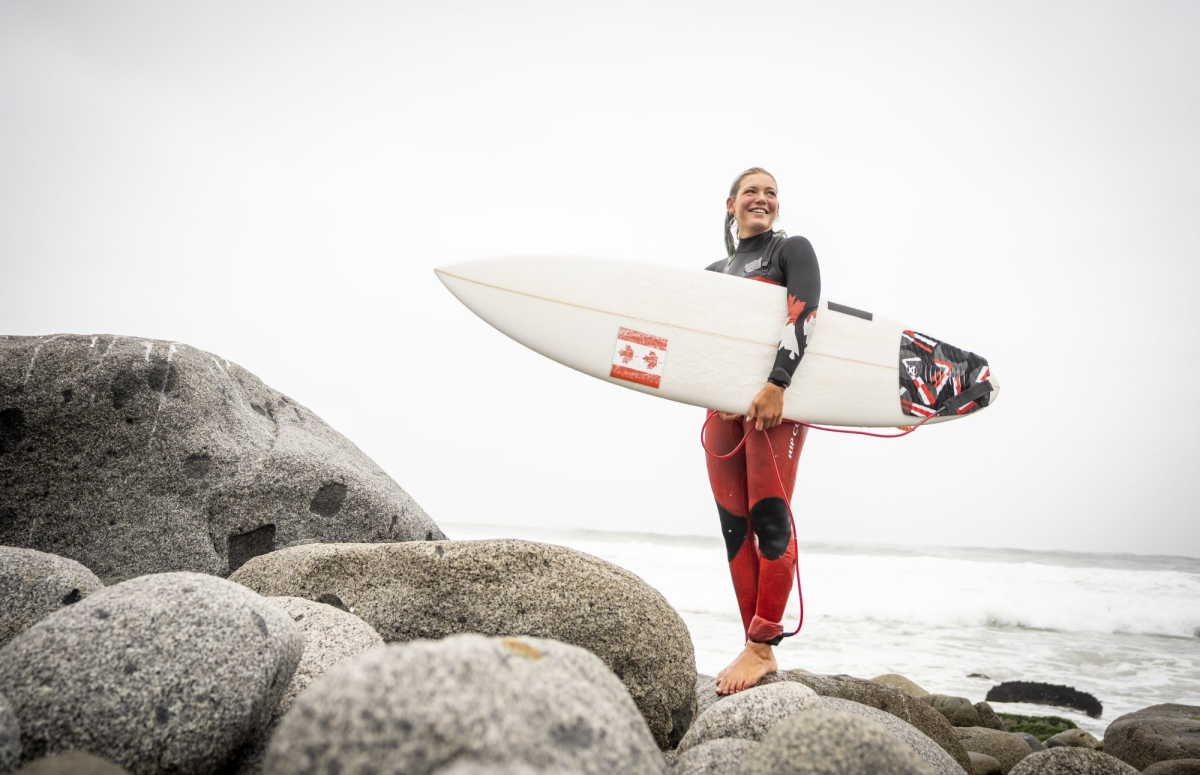 woman stands on rocks with a surf board