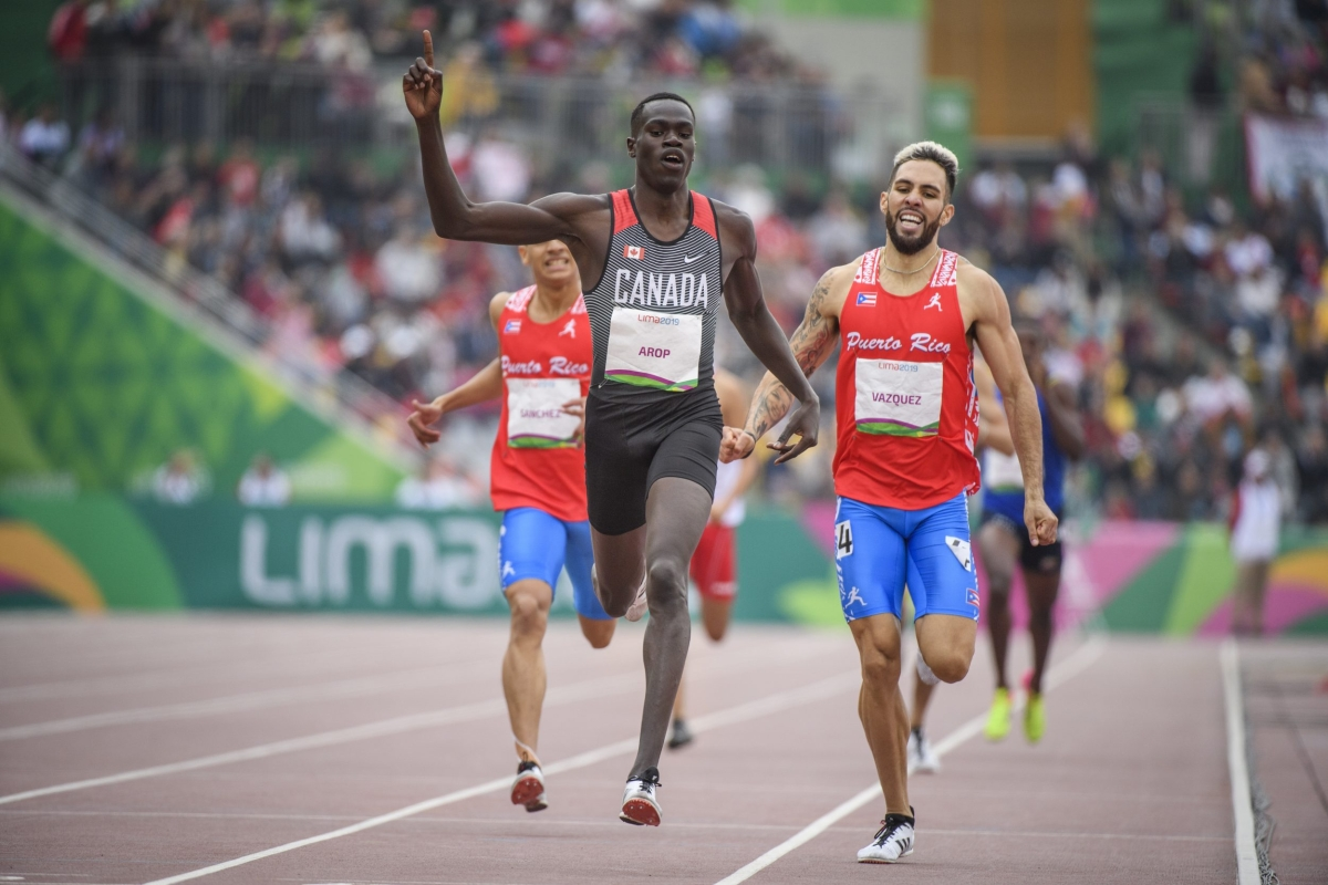 arop crosses the finish line with one arm up