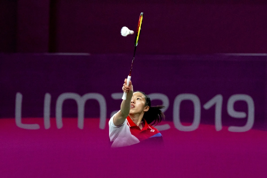 badminton player reaches for the birdie